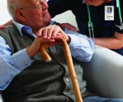 Senior man being visited by a nurse in a care home