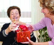 Happiness senior woman getting a red Christmas Present from a mature nurse.