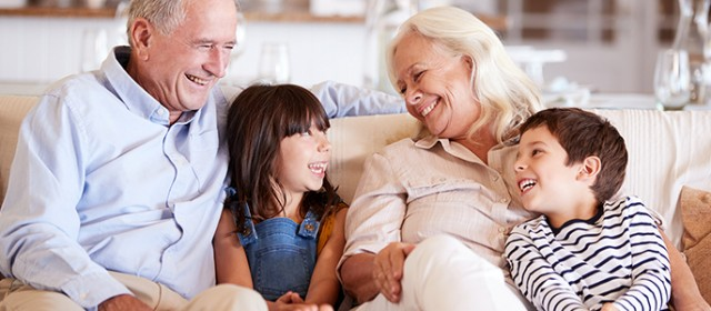 White senior couple and their grandchildren sitting on a sofa together smiling at each other