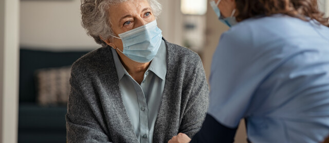 Elderly woman talking with a doctor while holding hands at home and wearing face protective mask. Worried senior woman talking to her general pratictioner visiting her at home during virus epidemic. Doctor explaining about precautionary measures during virus pandemic to old lady and takes care of her.